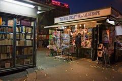 在evenin期间,人买一本杂志在邮政报刊亭, 免版税库存图片