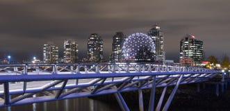 在False Creek的步行桥有科学世界的在背景中在街市温哥华,不列颠哥伦比亚省,加拿大 免版税库存照片