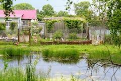 在farmer& x27前面的一个小池塘; s房子 免版税库存照片