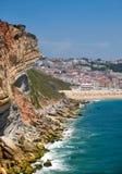 在Farol De Nazare之间的岩石和Nazare海滩和镇 图库摄影