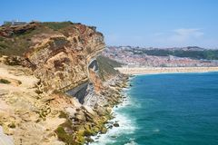 在Farol De Nazare之间的岩石和Nazare海滩和镇 免版税库存图片