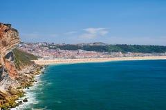 在Farol De Nazare之间的岩石和Nazare海滩和镇 免版税图库摄影