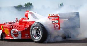 在Fiorano电路,意大利的法拉利F1迈克尔・舒马赫多福饼抽烟的轮胎 被递的一驾驶与波浪在多福饼期间 库存图片