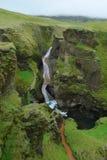 在Fjadrargljufur峡谷,河切口通过绿色岩石,冰岛的瀑布 免版税库存图片