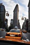 在Flatiron大厦之下的黄色出租车 图库摄影