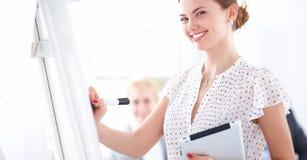 在flipchart的女实业家文字,当给介绍同事在办公室时 免版税库存照片