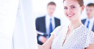 在flipchart的女实业家文字,当给介绍同事在办公室时 库存图片