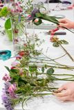 在floristics放置在与玻璃花瓶的桌的花店的花 免版税图库摄影