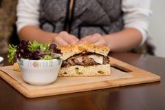 在focaccia面包的一个牛排三明治用旁边沙拉 免版税图库摄影
