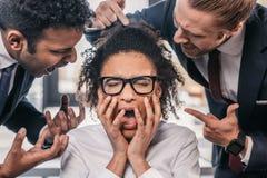 在formalwear的两个情感商人尖叫在女实业家在办公室 免版税图库摄影