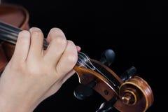 在fretboard小提琴的女性手 手指夹紧串 对音乐新闻覆盖面  关闭 黑色背景 图库摄影