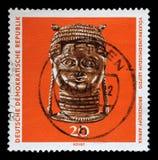 在GDR打印的邮票显示从非洲的古铜色头,莱比锡人种学博物馆  图库摄影