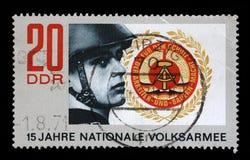 在GDR打印的邮票显示战士和徽章GDR的 免版税库存照片