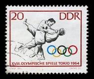 在GDR打印的邮票显示柔道,第18奥运会,东京64 免版税库存图片