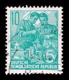 在GDR打印的邮票,展示两名工作者 免版税图库摄影
