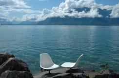 在Geneve湖的两把白色椅子 图库摄影