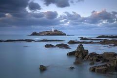 在Godrevy灯塔的日落在圣Ives海湾的Godrevy在前景,康沃尔郡英国的海岛与海滩和岩石上 免版税库存图片