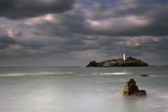 在Godrevy灯塔的风雨如磐的天空在Godrevy海岛上在圣Ives咆哮与海滩和岩石在前景,康沃尔郡英国 免版税库存照片
