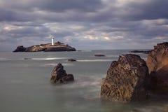 在Godrevy灯塔的风雨如磐的天空在Godrevy海岛上在圣Ives咆哮与海滩和岩石在前景,康沃尔郡英国 库存照片