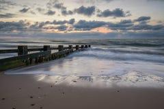 在groynes的日出在海湾 库存图片