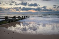 在groynes的日出在海湾 库存照片