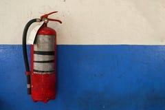 在grunge蓝色墙壁上的老灭火器坦克 库存图片