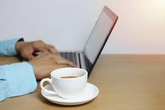 在Ha棕色木地板和计算机膝上型计算机的加奶咖啡杯子  免版税库存照片