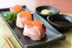 在Hamachi寿司的三文鱼獐鹿在与日本s一起的黑色的盘子 库存图片