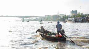 在Hau河,湄公河漂浮乘坐小船后面家,芹苴市浮动市场的市场客商,芹苴市的支流 免版税库存照片