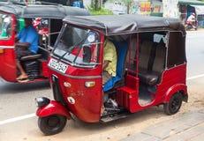 在Hikkaduwa街道上的两辆红色tuk-tuk车  免版税库存图片