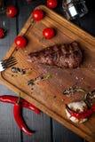 在hosper的被烘烤的格栅里脊肉 西红柿洒与在委员会的胡椒 免版税库存照片