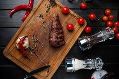 在hosper的被烘烤的格栅里脊肉 西红柿洒与在委员会的胡椒 库存照片
