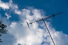 在house& x27的电视天线; s屋顶 并且蓝天 免版税图库摄影