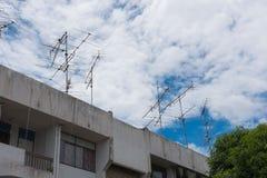在house& x27的电视天线; s屋顶 并且蓝天 库存图片