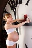 在hude时钟面孔,大手表附近的怀孕的白肤金发的妇女 免版税库存照片