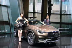 在Infiniti QX30 SUV的女性和男性时装模特儿 免版税库存照片