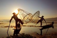 在Inle湖的传统渔夫剪影 免版税库存图片