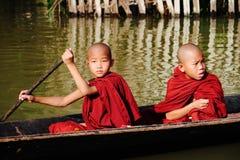 在Inle湖的年轻修士划艇 免版税库存照片