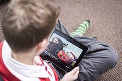 在iPad的观看的儿童的电影 库存图片