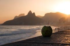 在Ipanema海滩的椰子饮料由日落 免版税库存图片