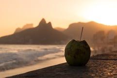 在Ipanema海滩的椰子饮料由日落 免版税图库摄影