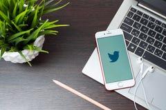 在iphone屏幕上的Twitter商标在膝上型计算机键盘安置在EarPods旁边在办公室 图库摄影
