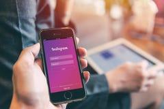 在iPhone的Instagram App与使用在巧妙的设备的人片剂背景特写镜头男性手举行社会网络 库存图片