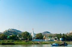在Irrawaddy河的小船有塔和村庄的 免版税库存图片