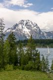 在Jenny湖的帆船有积雪的登上的Moran在背景中 免版税库存图片