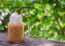 在juke玻璃杯子的被冰的咖啡在桌上 免版税库存图片