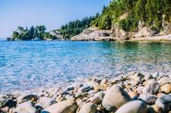 在Kalami附近的Pebble海滩与杉木和柏树和一条游艇在船锚在一个海湾在背景 corfu希腊海岛 免版税库存图片