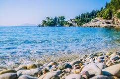 在Kalami附近的Pebble海滩与杉木和柏树和一条游艇在船锚在一个海湾在背景 corfu希腊海岛 免版税库存照片