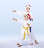 在karategi和帽子圣诞老人运动员打拳打胳膊 免版税库存图片