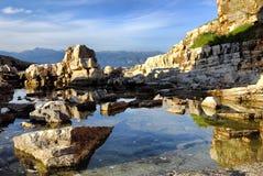 在Kassiopi的好的峭壁在科孚岛,希腊靠岸 免版税图库摄影